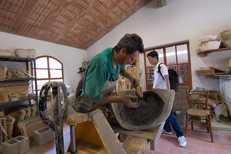 石膏型に原材料の土を充填転圧を行い製造している様子